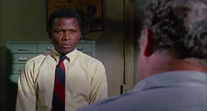Primary colors: Tibbs wears shades of red, yellow, and blue as he faces Gillespie in his office after Sam Wood brings him in for suspicion of murder.
