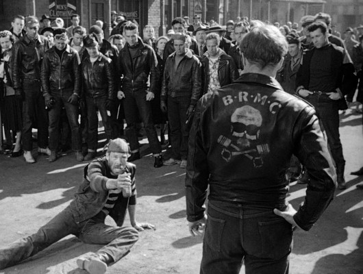 The members of B.R.M.C. and the Beetles surround their feuding leaders, dressed in a variety of leather jackets from Perfecto-style motorcycle jackets to A2-style flight jackets.