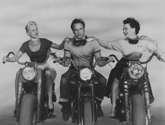 "Promotional photo of Johnny (Marlon Brando), flanked on his Triumph by Mildred (Peggy Mailey) and ""Britches"" (Yvonne Doughty), both on motorcycles of their own though only Britches was a fellow biker in the film; the blonde Mildred was the beauty shop owner who asked Johnny what he was rebelling against."