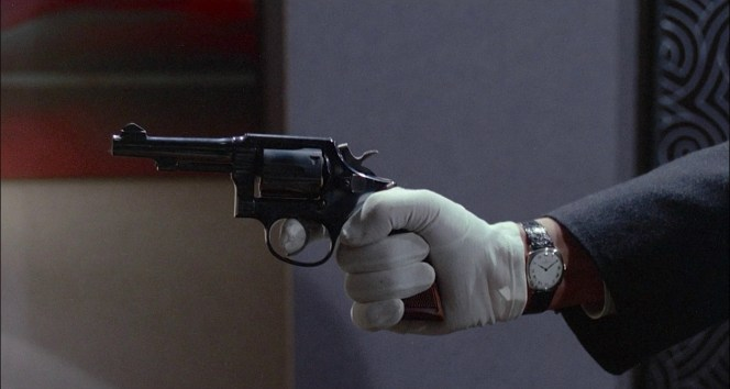 Framed in a shot to echo the first shooting, Costello fires his second Smith & Wesson Model 10 revolver at Olivier Rey.