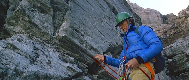 Clad in blue down jacket, green helmet, and durable cords, Dr. Hemlock ascends the treacherous Eiger Mountain's north face.