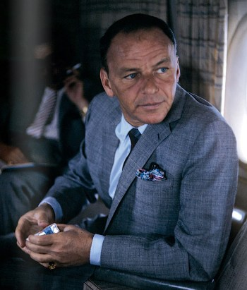 An introspective-looking Sinatra thumbs open a deck of Camels while flying to the Cal-Neva Lodge, 1962. Photo by Ted Allan.