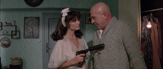 Eleana presents Zeno with his suppressed Walther P38K, evidently having little regard for his safety as her finger rests on the trigger of the double-action weapon.