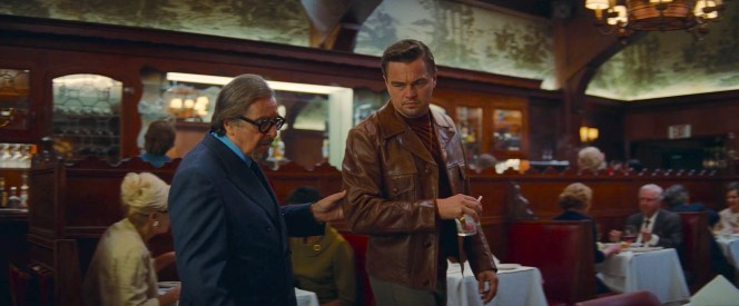While the energetic agent Marvin Schwarz jumps from the screen in his vibrant blues, Rick Dalton almost blends into the Musso & Frank atmosphere in his brown leather that matches the paneling.