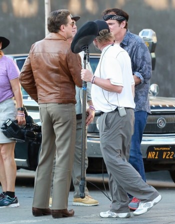 The distinctive Wrangler branding on the back right seam of Leonardo DiCaprio's costume trousers can be seen as he converses on set with Quentin Tarantino.