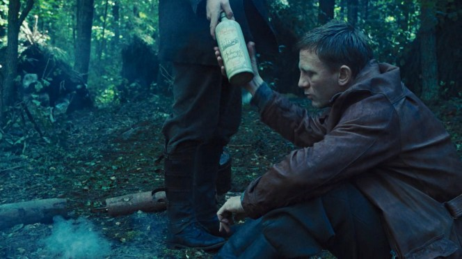 Zus hands Tuvia a bottle to drown his sorrows after an unpleasant task.