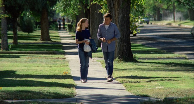 Holly carries Kit's jacket for him as he walks beside her in a rarely seen chambray shirt.