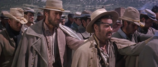 "Hardly the pride of the Confederacy, Blondie and Tuco's latest gambit lands them among bona fide rebels in a Union prison camp, ruthlessly run by Corporal Wallace (Mario Brega) and the newly ordained Sergeant ""Angel Eyes"" (Lee Van Cleef)."