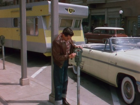 Nicky responsibly fills the parking meter not just for his Mercury but also the half-dozen spots occupied by his New Moon trailer.