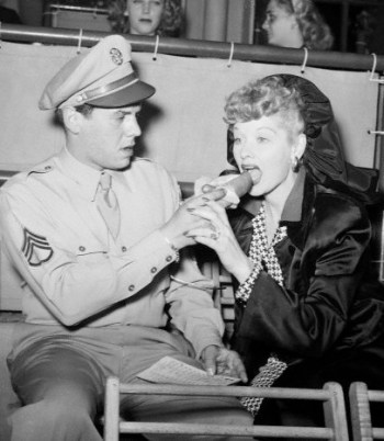 Clad in his U.S. Army service khaki uniform, Staff Sergeant Desi Arnaz offers Lucille Ball a hot dog at the Santa Anita race track, June 1945.