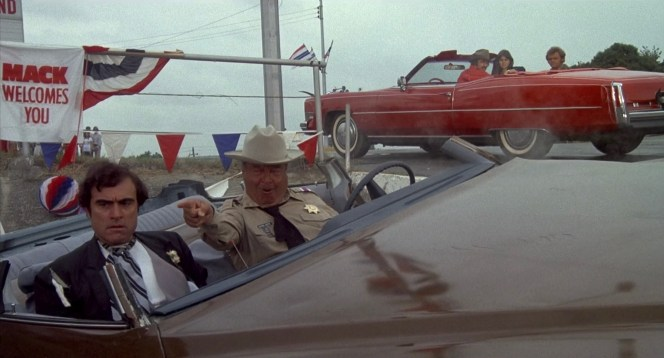 From their perch in Big Enos Burdette's Cadillac, the Bandit, Frog, and Snowman observe the blustering Buford T. Justice in what's left of his police cruiser.