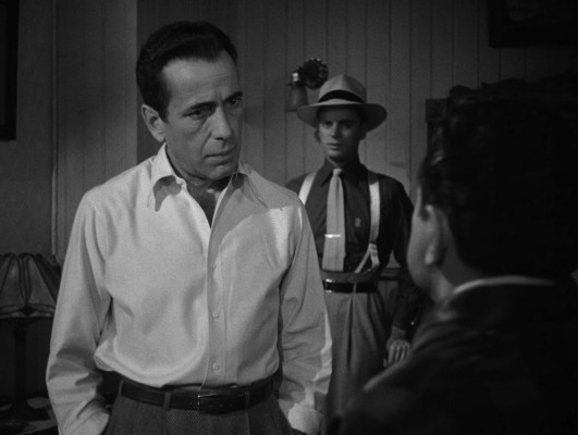 """Note how subtle Frank's plain white shirt looks when compared to Toots over his left shoulder, sporting monogrammed dark silk shirt, contrasting light knitted tie tucked into his """"Hollywood"""" trousers supported by belt and braces, not to mention that wide-brimmed Panama hat or his spectator wingtips."""