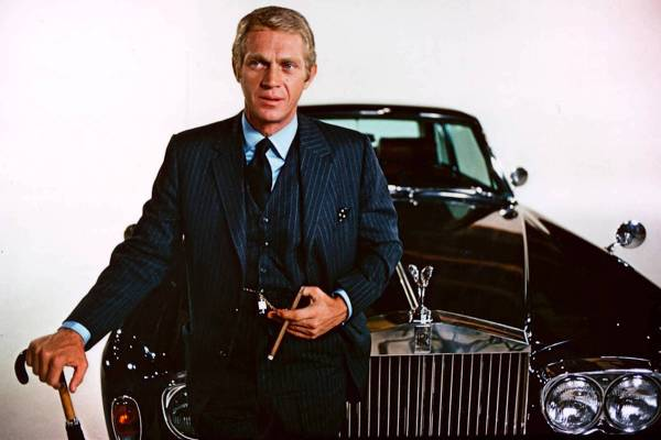 Steve McQueen poses with his character's luxurious Rolls-Royce Silver Shadow coupe to promote The Thomas Crown Affair.