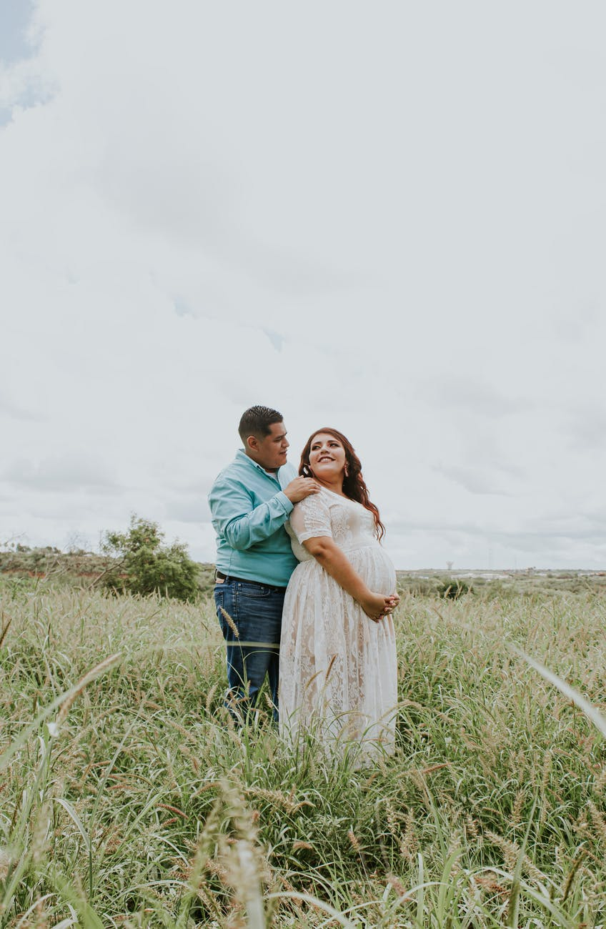 happy man embracing expectant beloved in field