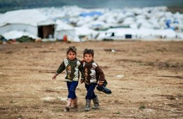 Syrian boys, whose family fled their home in Idlib, walk to thei