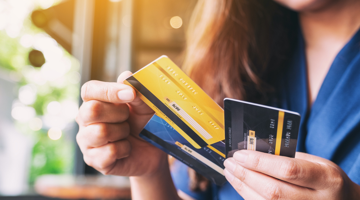 a woman holding and choosing credit card to use