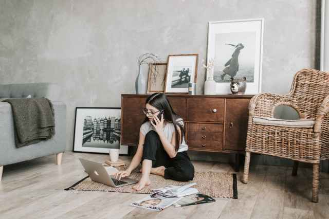 focused young woman with laptop and smartphone in modern apartment