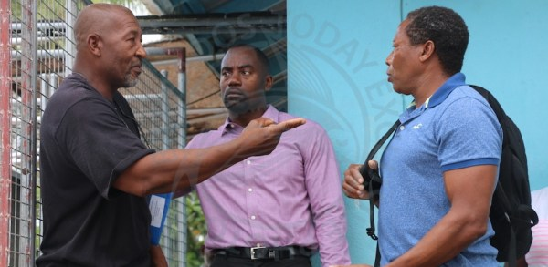 Boat owners and fishermen Owen Moore (left) and his brother Wilfield Moore (right) express their concerns to Minister of Maritime Affairs and the Blue Economy Kirk Humphrey during a tour of the Millie Ifill Fish Market in Weston, St James this morning.