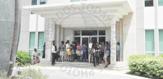 Workers standing outside of the Barbados Statistical Department after a pungent odour emanated from the fifth floor of the Baobab Towers, Warrens St Michael this morning.