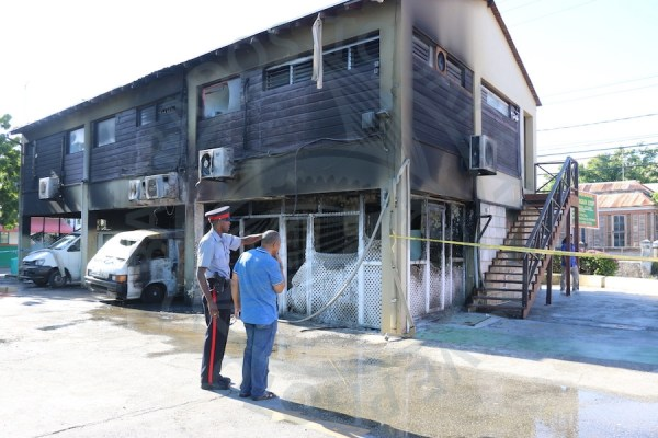 A Royal Barbados Police Force officer taking owner Juan Watson on a walk through of the damages from the blaze at Ice Complex located at Hastings, Christ Church.