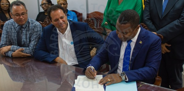 Minister of Energy and Water Resources Wilfred Abrahams (right), signing Government's Energy Efficient Retrofit of Public Sector Smart Energy Programme agreement, as Chief Executive Officer of Caribbean LED Lighting Inc (centre), and Managing Director of the Barbados Light & Power Ltd Roger Blackman (left) look on.