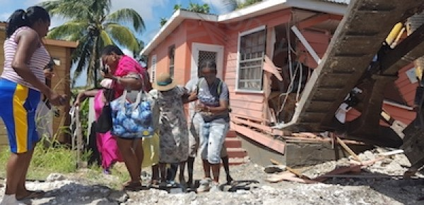 Residents assisting 97-year-old mother Clarine Edwards (centre) from her house.