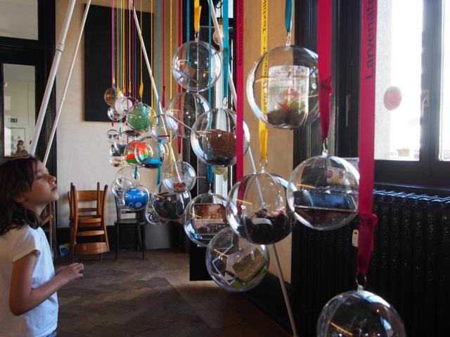 Ausstellung an der Zielstation: Plexiglaskugeln mit Objekten aus Ateliers und Werkstätten