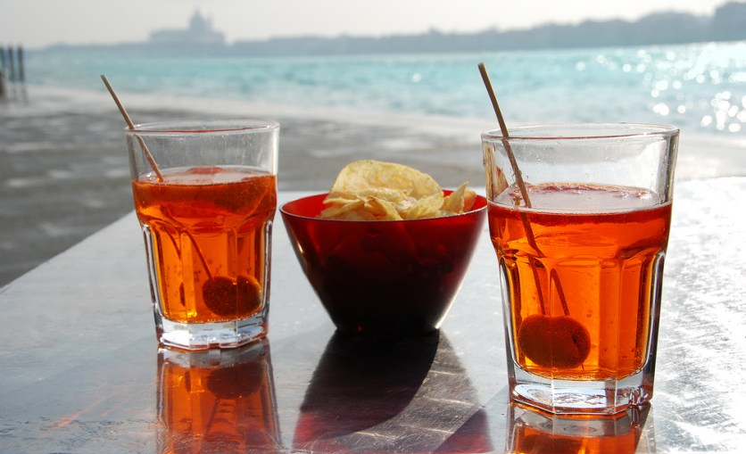 Pour prosecco, campari and soda over ice.  Add an olive or slice of orange.  Enjoy as the sun sets over the Grand Canal.