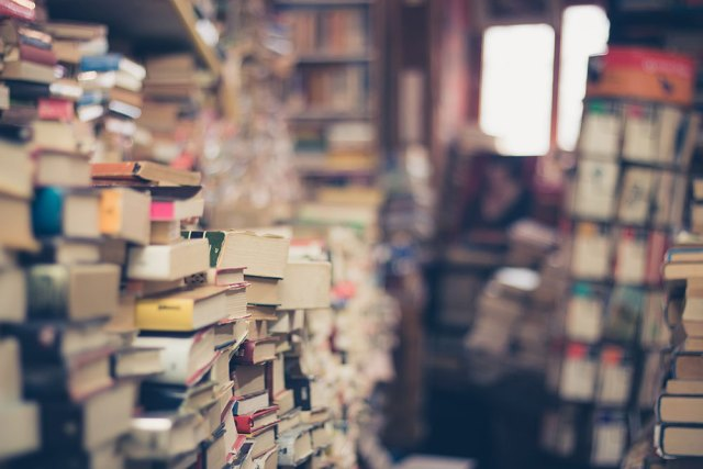 A book shop full of books piled high