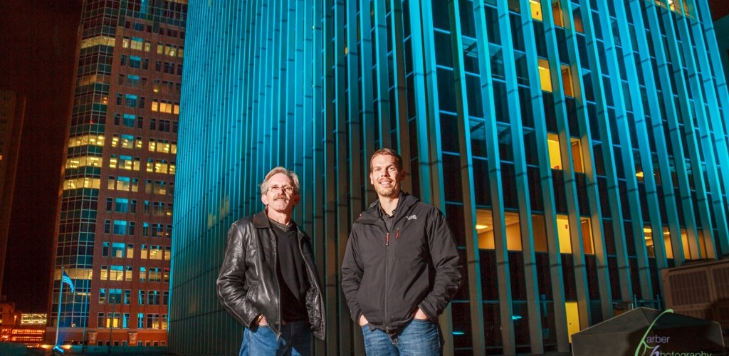 An environmental portrait of Mike and Kris in front of the Financial Center who re-lit the building, changing the Des Moines, Iowa skyline