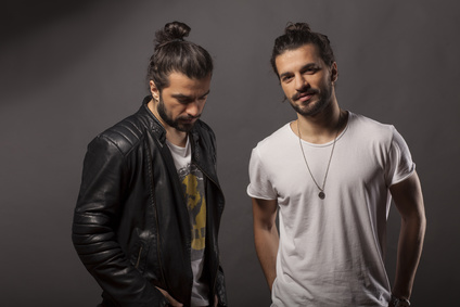 Two handsome young men with a beard and long hair in a bun