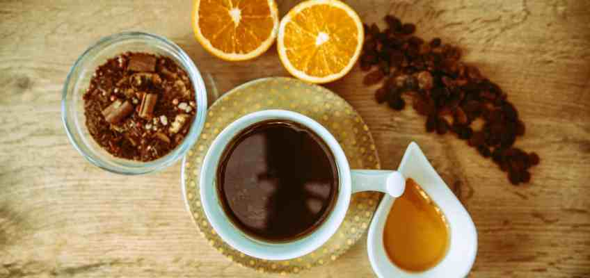 overhead image with oranges, spices like cinnamon, pepper, raisins, a jar with honey and a mug with a hot drink