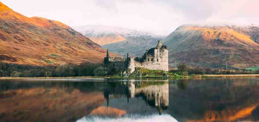 A scottish castle in front of a lake and its reflection in an autumn atmosphere.