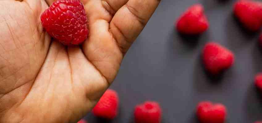 A hand holding a raspberry