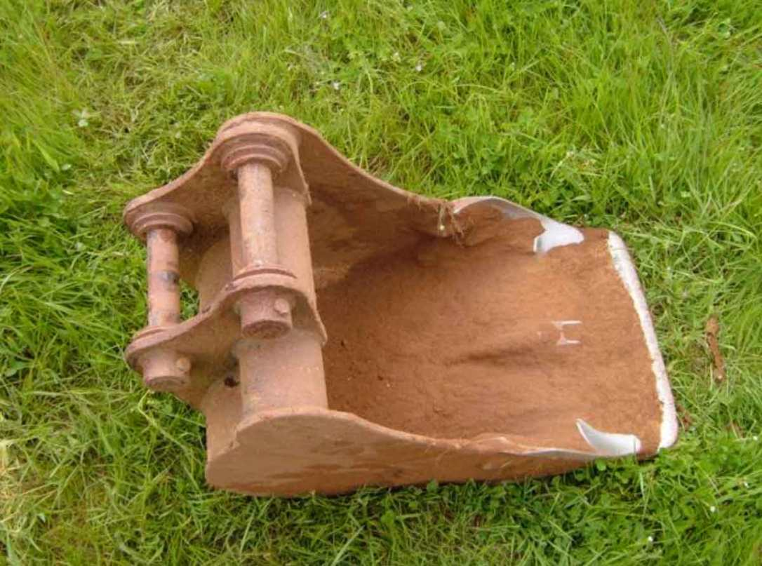 a toothless digger bucket on the grass at barefoot glamping Cornwall