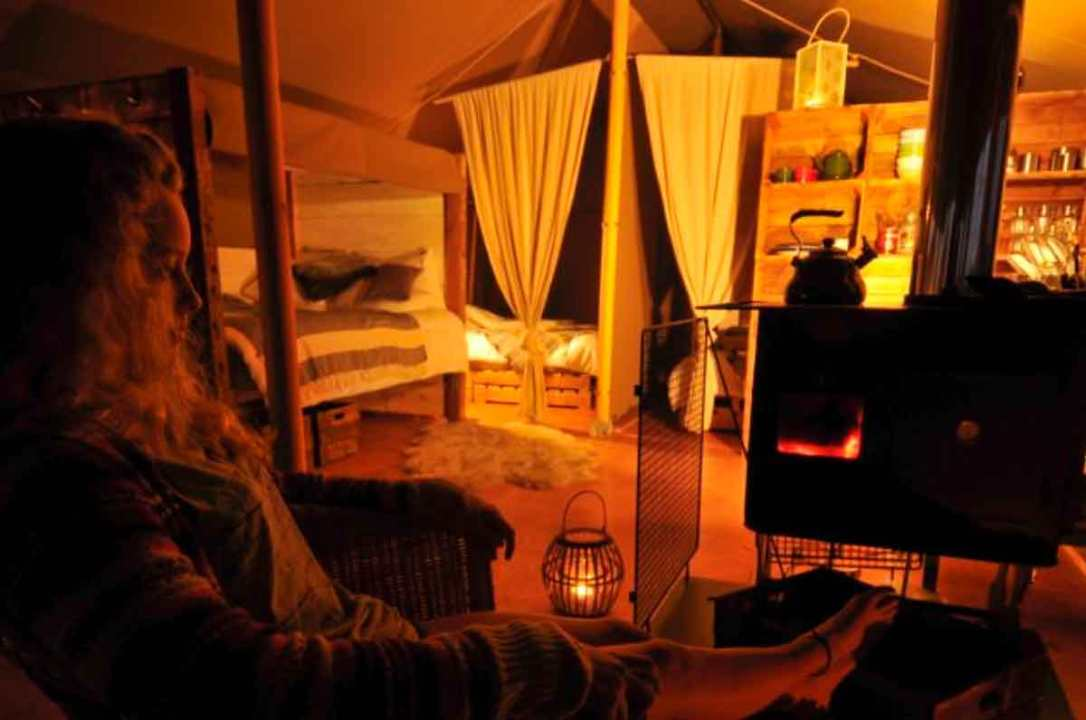 girl sitting by the warn wood stove in Hobie safari tent at barefoot glamping Cornwall