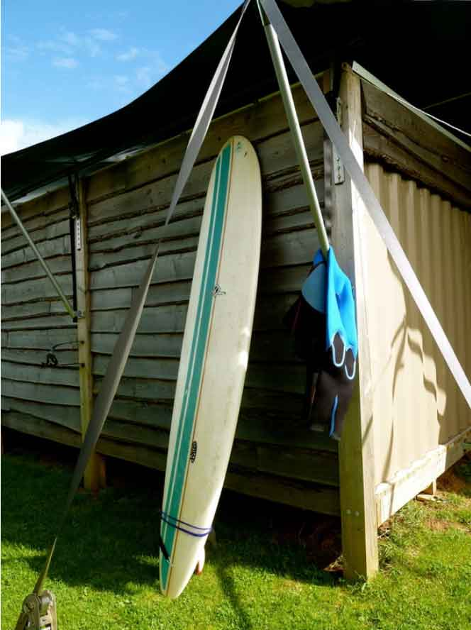 surf board and wetsuit outside rusty the tin tent shipping container at barefoot glamping Cornwall