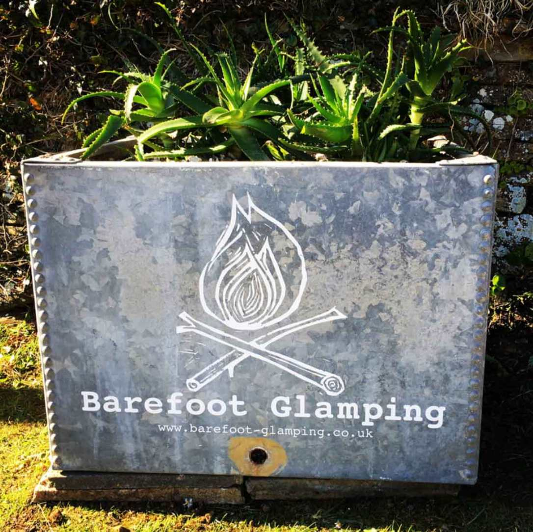 an up cycled water tank plater with barefoot glamping graphics in Cornwall