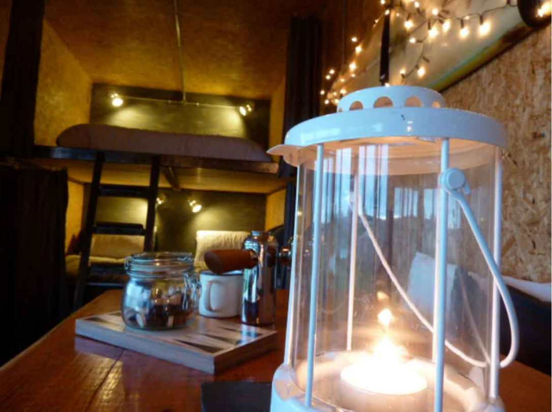 the cosy glow in Rusty the tin tent with lanterns and fairy lights