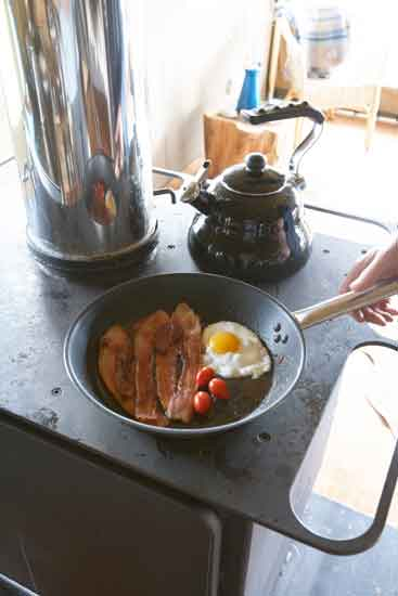 a full English breakfast cooking on the wood stove in the safari tent