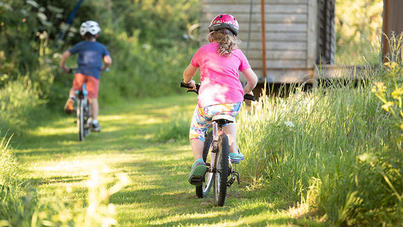 Kids riding bikes along the mown path to woody safari tent