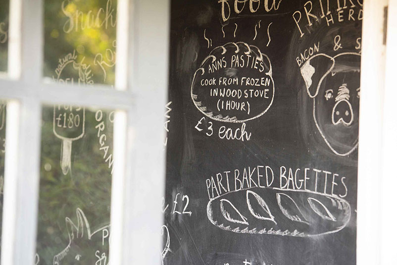 looking through the honesty shop door at the chalk board menu