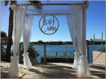 Wedding arbour with white chiffon & laser cut wedding sign attqached to arbour. Ebb Restaurant, Sunshine Coast.