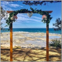 Timber wedding arbour decorated with artificial green ivory, flowers & love heart. Shelly Beach, Caloundra.