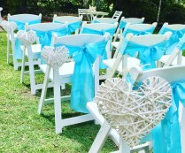White wicker love hearts for wedding aisle decor. Light blue chair sashes.
