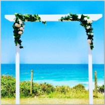White timber wedding arch styled with faux greenery and white faux flowers. Point Arkwright, Coolum.