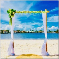 Bamboo wedding arch styled with white chiffon and faux tropical greenery and flowers. Double Bay Beach, Kawana Island.
