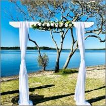 White timber wedding arch styled with chiffon, white rose and greenery faux flowers. Chambers Island, Sunshine Coast.