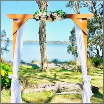 Natural timber wedding arch styled with faux pink and white peony flowers and greeneryand white chiffon. Location: Lake Weyba