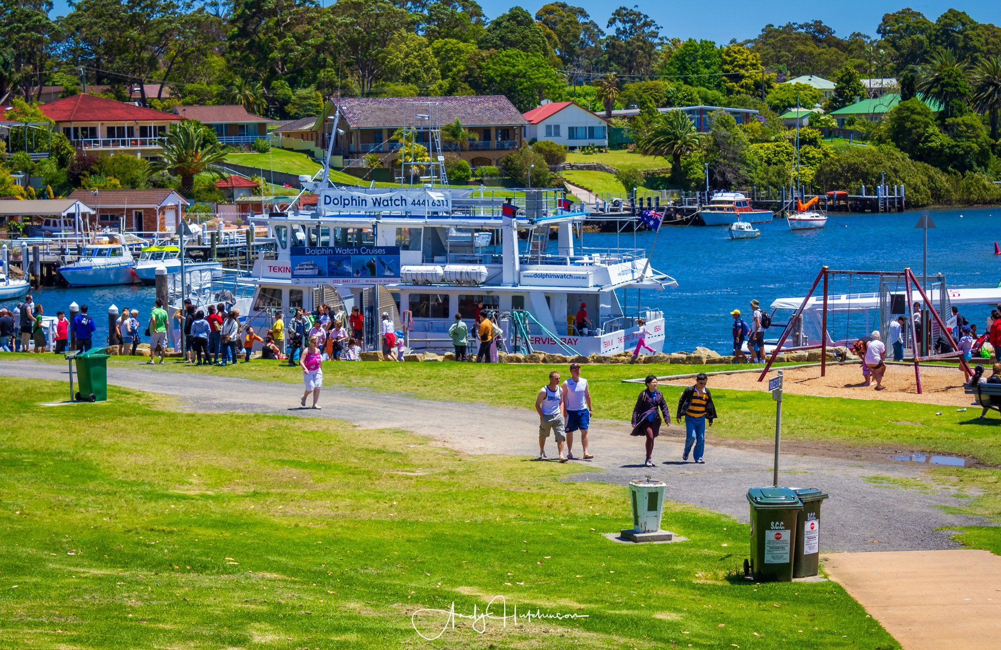 Tourists walk through Voyager Park near the public wharf in Huskisson